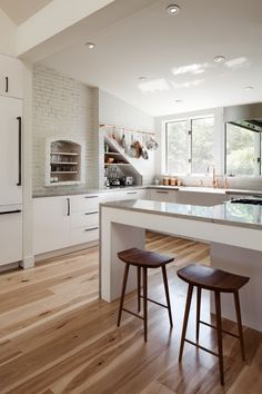 Hickory flooring brings color, interest, and warmth to a modern white kitchen.