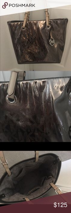 Michael Kors Bag Large tote bag. Only used lightly last season. Very clean and well cared for . Metallic silver/ grey color goes with everything. Lining clean. Two inside pockets and one large zip compartment. Dust bag and MK Card included. Perfect for summer. ❌FIRM UNLESS BUNDLED FOR 10% discount❌ MK Bags Totes