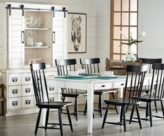 "A great dining table has always been the center of family life and Joanna's Farmhouse Table will be just that with its nostalgic look and worn-in Jo's White finish. It has two ""keeping drawers"" on each side for a bit of storage and square tapering legs. For contrast, Jo grouped it with her comb back Windsor Spindle Chairs in Jo's Black painted finish.  The Farmhouse Buffet was inspired by a vintage drugstore cabinet and has a ton of drawer storage. Its Hutch top has shelves behind barn door…"