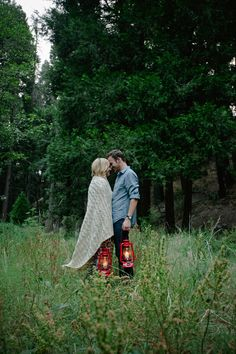 Couple in love holding lanterns in a field by Kristin Rogers Photography - Stocksy United