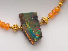 Australian boulder opal with oranges, greens, teals and reds on smooth graduated rondelles of mandarin garnet with 18K accents. ElleSchroeder.com