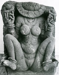 Kali worship: Indian Stone sculpture of naked female seated figure displaying the yoni.