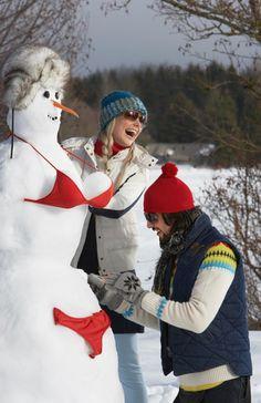 Couple building snow woman in bikini (© Radius Images/Corbis)