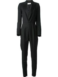 Macacão social preto. A parte superior lembra um blazer. O toque feminino fica por conta da cintura marcada e das demais peças complementares na montagem do look, como os acessórios e o sapato.