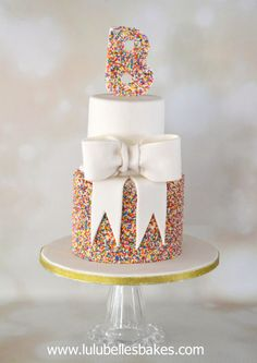 2 Tier sprinkle cake with large white sugar paste bow