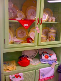 Yellow dishes display nicely in this green hutch