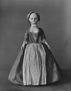 1735 English doll wearing silk gown, with linen apron