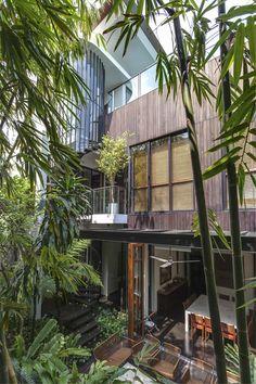 ジャングルのような庭園につながる全開口の折れ戸のあるダイニング
