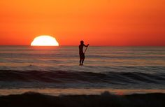 Go paddle-boarding at sunset