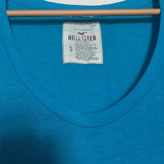 Clearance‼️ Blue hollister tee Blue hollister tee shirt. Lower rounded neck. Brighter blue than it looks in the picture. Small amount of discoloration on one underarm but barely noticeable Hollister Tops Tees - Short Sleeve