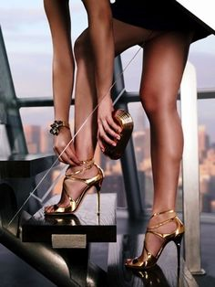 Great legs in little black dress and gold strappy high heels