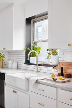 White and gold kitchen features a window framed by a black windowsill positioned above a farmhouse sink with a brushed brass gooseneck faucet fixed to a marble countertop placed against a white subway tile backsplash and on top of white shaker cabinets donning brass hexagon knobs.