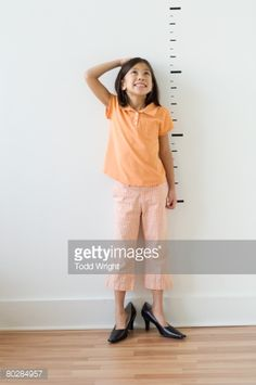Stock Photo : Asian girl wearing mother's shoes in front of height markers