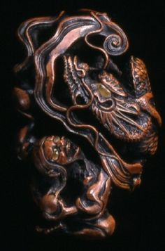 Arhat Panthaka (J: Handaka Sonja) with dragon. Japanese netsuke made of wood, eyes inlaid in amber. Signed. Made by Toyomasa 豊昌. Early 19thC