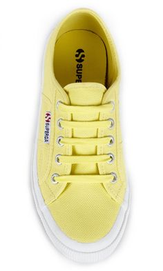 Iconic, bright yellow canvas sneakers by Superga. Italian-made with tonal ties, logo-embossed grommets and a wide rubber sidewall.
