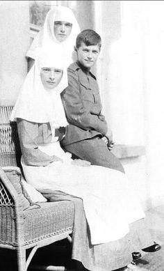 Grand Duchesses Olga Nikolaevna and Tatiana Nikolaevna, in their nurses uniforms, with their brother Tsarevich Alexei Nikolaevich.