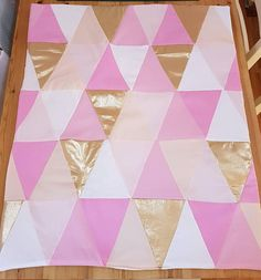 Beautifully handmade baby quilt with triangle patchwork in beautiful gold, peach and mixed pinks, with a plain white backing. A very different and unique quilt, one of a kind.