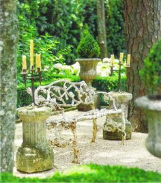 """Pair of 18th-c. French iron candelabra on stone columns, c. 1750, flank 19th-c. faux bois garden bench with original paint; stone 19th-c. urns; white hydrangeas brighten background; crushed limestone underfoot."" Interior design by Pamela Pierce, Pierce Designs and Associates. Landscape design by Danny McNair. Photography by Peter Vitale. Text by Tom Woodham. ""European Influence"" Veranda (July - August 2009)."