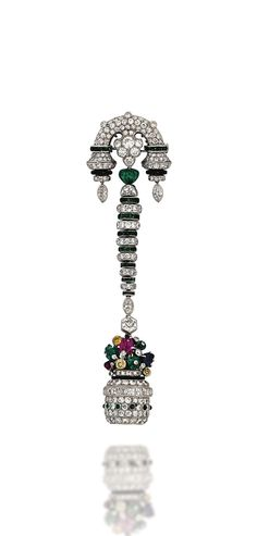 A FINE ART DECO GEM AND DIAMOND LAPEL WATCH -  Designed as a brilliant and French-cut diamond, emerald cabochon and black enamel stylised vase, with yellow diamond, carved sapphire, ruby and emerald flower cluster, enclosing a watch with circular silvered dial, black painted Arabic numerals and blued-steel hands, suspended from a graduated buff-top emerald and diamond line and similarly-set arched surmount, mechanical movement, circa 1925.
