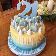 Vanilla sponge cake filled with buttercream, and finished with a white chocolate drip ganache, chocolate ganache filled macarons and meringue kisses.