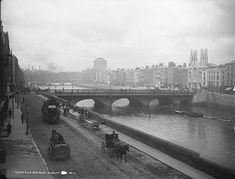 Men repair the pavement along quays in front of Grattan Bridge. #Irish #History