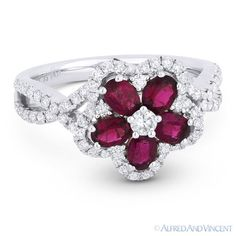 The featured flower-design ring is cast in 18k white gold and showcases a round brilliant diamond center, oval cut ruby petals, & round cut diamond accents paved on the flower design and on both sides of the ring's band.  #diamonds #gemstones #18kgold #18kjewelry #whitegold #rings