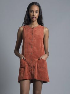 The Twiggy pinafore is cut in a flattering sleeveless shift shape and features 2 rounded pockets to the front and is fully lined. The dress features a copper brass toned pop button front. Style with y