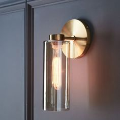 The special finish on this Glass Cylinder Sconce is mirror-like when turned off and see through when lit. Its unique luster adds a touch of radiance to any room.