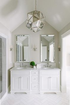 Charming white and tan bathroom boasts an antiqued mirrored light pendant hung from a vaulted ceiling over white herringbone marble floor tiles leading to a white dual washstand donning polished nickel pulls and a white quartz countertop.