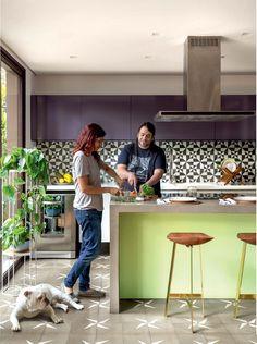 Cozinha  cheia de cor com ladrilhos hidraulicos e armarios berinjela combinando com o verde da bancada.