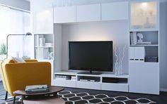 Un salón con una combinación amplia que consta de un mueble para TV blanco, estanterías con puertas de vidrio esmerilado y puertas y frentes...