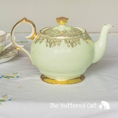An elegant teapot made by Shore and Coggins pottery in England in the trade name Queen Anne, in pastel green and decorated with gold grape bunches and vines. The teapot has a tiny nick on its lid, see last photo, top left. Otherwise it is in good, used condition with no chips, cracks