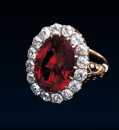 """Queen Marie José Royal Ruby Ring, c.1870, Gold, Silver, Diamonds, 8.48ct ruby. """"A late 19th century highly important Burma ruby and diamond-set cluster late ring, the oval bezel set with a step-cut Burmese (Myanmar) ruby weighing 8.48 cts surrounded by a border of sixteen old brilliant-cut diamonds secured by claws supporting the gold hoop terminating in shoulders"""""""