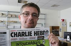 In this Sept.19, 2012 file photo, publishing director of the satirical weekly Charlie Hebdo Stéphane Charbonnier - also known as Charb - displays the front page of the newspaper as he poses for photographers in Paris. Masked gunmen stormed the Paris offices of Charlie Hebdo Wednesday January.7, 2015, killing 12 people including Charb, before escaping.