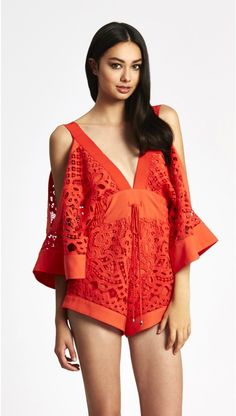 this playsuit sports japanese inspired wide kimono sleeves finishing below the elbow, creating volumne and exposing the shoulder to create a fun and flirty...