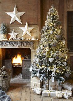 Love this rustic Christmas tree & the overall decor—esp the fire andirons with the white stars.