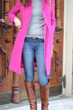 Bright pink coat, gray shirt, jeans, leopard belt, riding boots, and a statement necklace