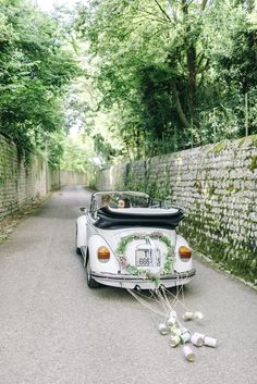 White Beetle Wedding Car with Tin Cans - Sarah-Jane Ethan Photography | Destination Wedding with Outdoor Reception at Borgo dei Conti della Torre in Italy | Rustic Styling by Santi Group | Stefano Blandaleone Bridal Gown
