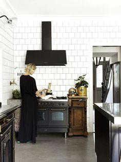 Modern kitchen with full wall white tile, concrete floors, and a vintage looking stove