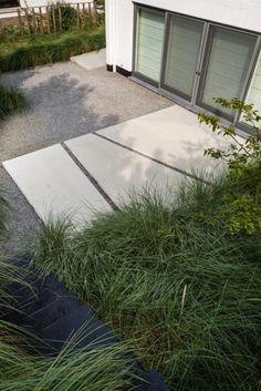 Origineel lijnenspel en mooie combinatie van minimalistische materialen en beplanting. #voortuin #modern #siergras #beton
