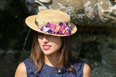 Canotier de copa baja adornado con cinta de sinamay negra y hojas y flores de terciopelo en tonos rosa, violeta y azul claro. Se ajusta fácilmente con una cinta de organza.