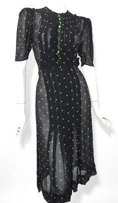 Sheer black silk 30s dress with mocha tan print, wide pleats top to bottom and gorgeous, beveled glass emerald green button accents. Snaps at neckline and up left side, no flaws.