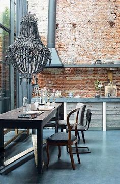loft style kitchen with very high ceilings, exposed brick wall,large beaded chandelier over wood table. Industrial chic look
