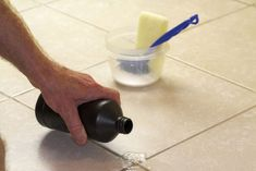 Hand pouring hydrogen peroxide on bathroom floor tile grout.