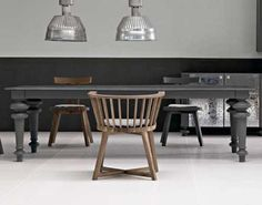 the dark grey table looks great with the wooden chairs and industrial lighting