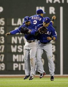 From left, Texas Rangers left fielder Delino DeShields, center fielder Leonys Martin and right fielder Shin-Soo Choo jump to celebrate the team's 2-1 victory over the Boston Red Sox in a baseball game at Fenway Park in Boston Wednesday, May 20, 2015. (AP Photo/Elise Amendola)