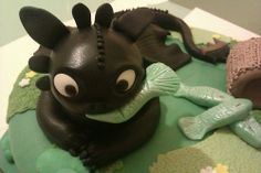 Toothless cake topper featuring toothless eating fish