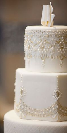 Say Yes to the Cake - For our very own Kleinfeld bride, there was no question that the dress be the inspiration for the wedding cake.  But when it came to the topper, a frosting ribbon from her shoes took the cake!  Photo Credit:  Olive Juice Studios