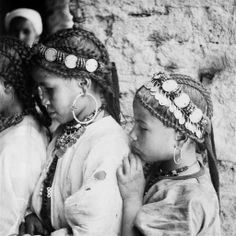 Africa | Imerrhane girls with their sophisticated hairstyles decorated with headbands trimmed with silver coins and coral beads.  Dades Gorges, Skoura, Dades Valley, Morocco.  ca. 1934 - 1939. | ©Jean Besancenot.