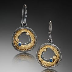 Jenny Reeves uses ancient techniques to create modern fine art jewelry. Her work is created by fusing layers of sterling silver, 14K, and 18K gold; the process develops organic stone-like textures and wood-grain patterns that are balanced by geometric lines and classical proportions. Patinas create contrast; colored stones and diamonds bring the pieces to life. Each is crafted from recycled precious metals with meticulous attention to detail.  See more of her work here…
